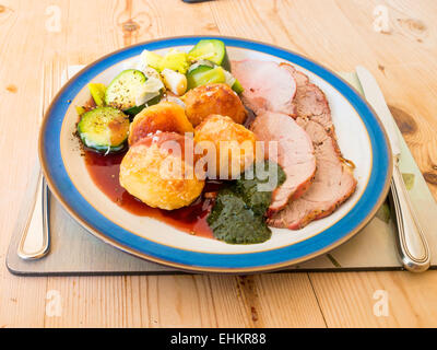 English Sunday lunch roast lamb broccoli leeks and gravy served with mint sauce on a blue and white plate wooden - Stock Photo