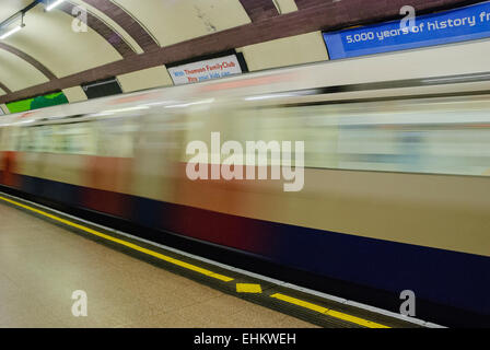 Train speeds through a London Underground tube station - Stock Photo
