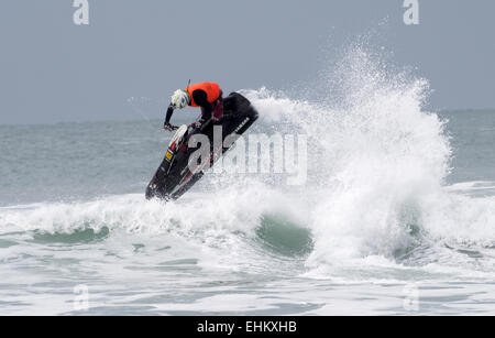 Male jet ski competitor performs aerial action moves in large breaking surf on Newquay Fistral beach - Stock Photo