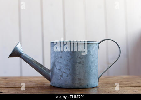 watering can on a wooden table - Stock Photo