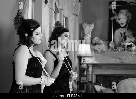 Young lady wearing vintage clothing in deep thought with reflection in mirror and a picture of Marilyn Monroe  black - Stock Photo