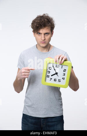 Angry young man with curly hair pointing on the clock - Stock Photo