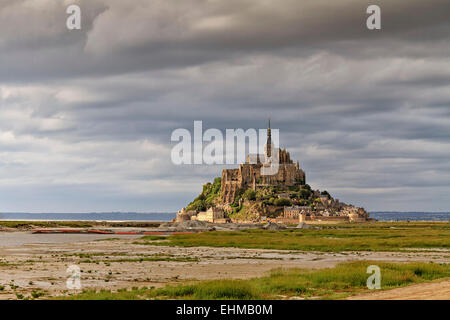 Le Mont-Saint-Michel with the Benedictine Abbey on the rocky island of Mont Saint-Michel in the evening light - Stock Photo