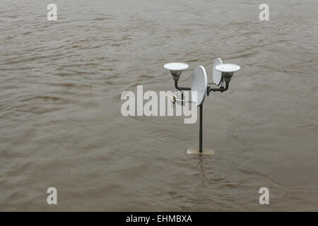 Street lamppost with a satellite dish partially flooded by the swollen Vltava River in Prague, Czech Republic. - Stock Photo