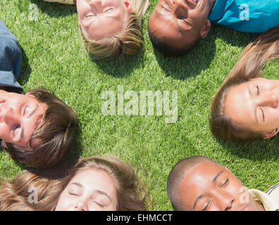 High angle view of teenagers sleeping on grass lawn - Stock Photo