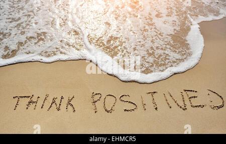 think positive written on sand beach - positive thinking concept - Stock Photo