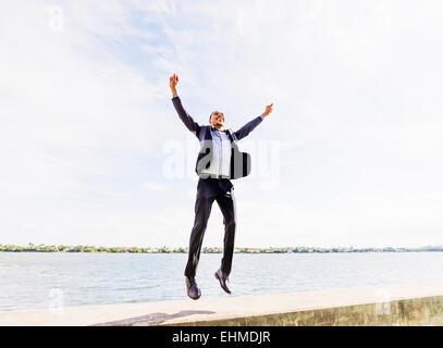 Black businessman jumping for joy outdoors - Stock Photo