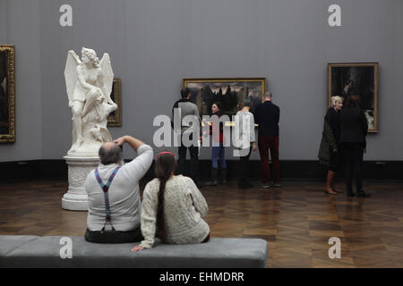 Visitors look at the painting 'Isle of the Dead' (1883) by Swiss symbolist painter Arnold Böcklin displayed in the - Stock Photo