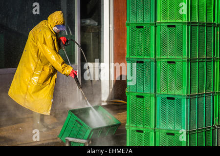 Worker cleaning green boxes in yellow safety protective equipment - Stock Photo