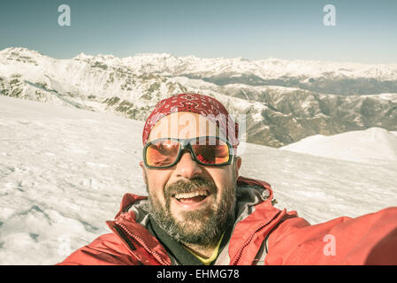Adult european man taking selfie on snowy slope with the beautiful snowcapped italian Alps in the background. Toned - Stock Photo