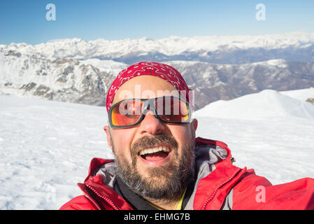 Adult european man taking selfie on snowy slope with the beautiful snowcapped italian Alps in the background. Natural - Stock Photo