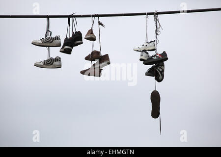 Old boots hang on the electrical cable in Letna Park in Prague, Czech Republic. According to the local legend, teenagers - Stock Photo