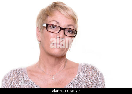 Distrustful stern middle-aged woman wearing glasses with a serious unyielding expression looking intently at the - Stock Photo