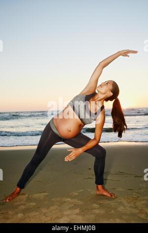 Pregnant Hispanic woman practicing yoga on beach - Stock Photo