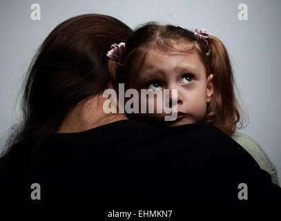 Thinking sad daughter embracing her mother and looking up on dark background - Stock Photo