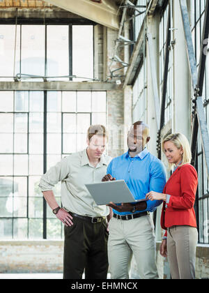 Business people using laptop in warehouse