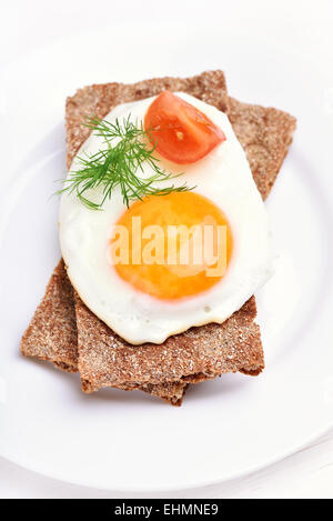 Fried egg, dill and tomato slice on crispbread, top view - Stock Photo