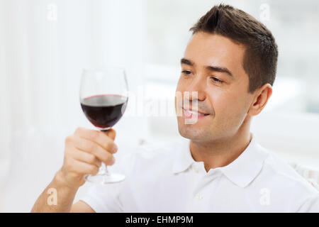 happy man drinking red wine from glass at home - Stock Photo