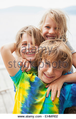 Caucasian children smiling together outdoors - Stock Photo