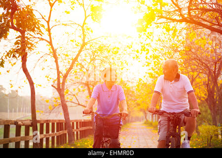 senior couple on cycle ride in the park - Stock Photo