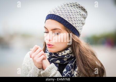 Woman blowing on his hands. - Stock Photo