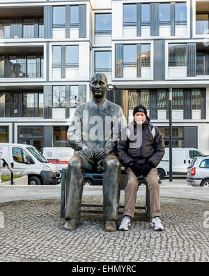 senior man sits with  statue of man seated on bench in Mitte, Berlin - Stock Photo
