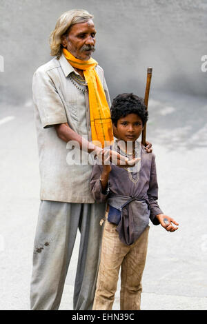A blind man begging for money with the help of a young boy on September 11, 2008 in the streets of Udaipur, India - Stock Photo