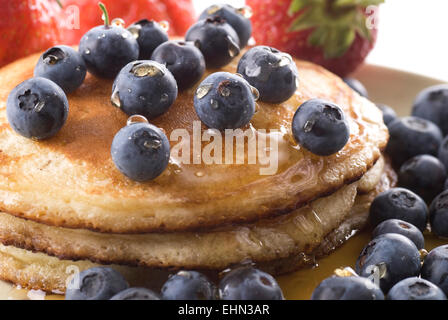 Pancakes with fresh blueberries and syrup on a plate.  Strawberries in the background. - Stock Photo