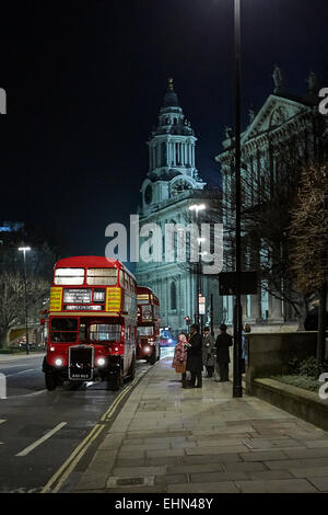 London Transport classic red RT and RM Routemaster double deck buses in front of St Paul's cathedral at night - Stock Photo