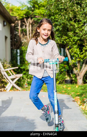 Children on scooters outdoors. - Stock Photo