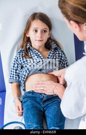 Doctor examining a young girl's abdomen. - Stock Photo
