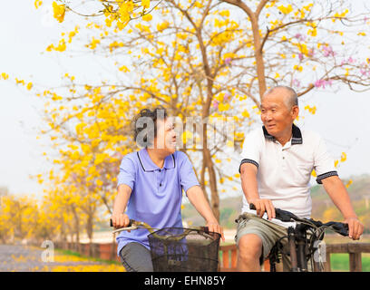 happy asian senior couple ride on bicycle  in the park - Stock Photo