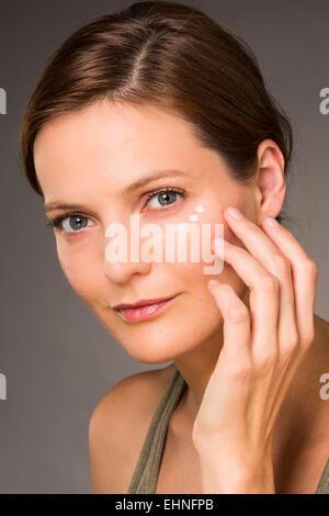 Woman applying anti-wrinkle cream around the eyes. - Stock Photo