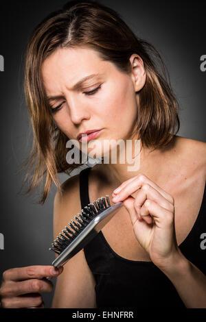 Woman brushing her hair. - Stock Photo