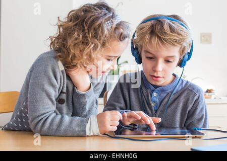 5 year old girl and 8 year old boy using tablet computer. - Stock Photo