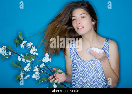 Woman with hay fever blowing her nose. - Stock Photo