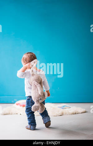 Toddler walking away from camera with rabbit toy over shoulder - Stock Photo