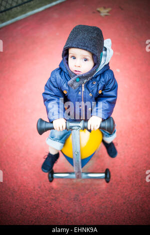 18 month-old baby boy in a playground. - Stock Photo
