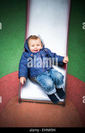 18 month-old baby boy on a slide in a playground. - Stock Photo