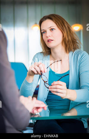 Doctor discussing with a female patient. - Stock Photo