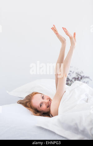 Woman waking up and stretching in bed. - Stock Photo