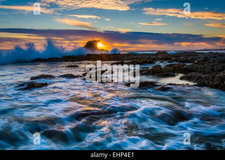Waves and rocks at sunset, at Little Corona Beach, in Corona del Mar, California.