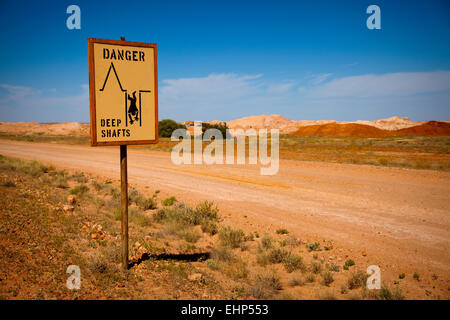 A road sign warning of deep mineshafts in opal mining country, Coober Pedy, Australia - Stock Photo