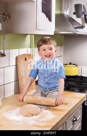 Beautiful boy sitting on the kitchen counter holding a rolling pin. making bread or pizza. - Stock Photo