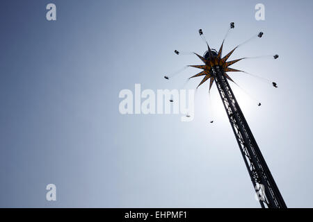 spinning star flyer ride in amusement park - Stock Photo