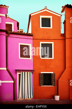 two houses painted in striking colors in Burano, small island near Venice - Stock Photo