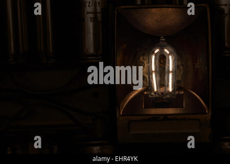 glowing filament of a 1000 quartz halogen bulb with flaked metal and heat damage to the reflector and heat dispenser - Stock Photo