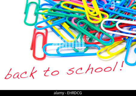 sentence back to school written in red on a white background, with many paperclips of different colors - Stock Photo