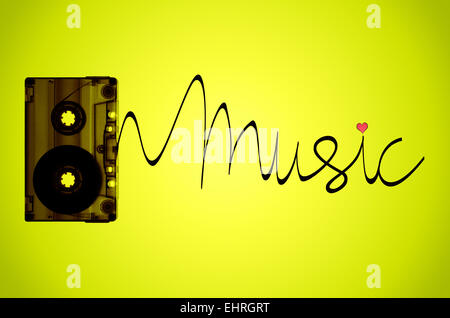 A cassette tape on a lime green back-lit background with tape coming out of the cassette to spell the word music. - Stock Photo