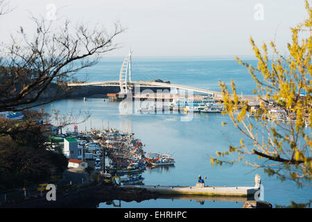 Asia, Republic of Korea, South Korea, Jeju island, Seogwipo city, harbour boats and Saeyeongyo bridge - Stock Photo